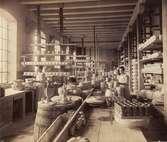 Rörstrands fabrik. Fabriksinteriör, verkstadshuset. Kvinnor och män i arbete vid bänkar. Porslin i långa rader längs bord och hyllor.