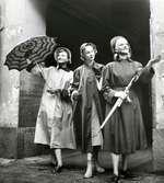 Tre kvinnor i regnkappor, regnmössor och paraplyn.