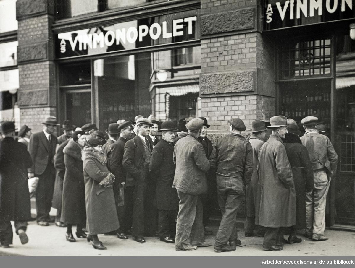 A/S Vinmonopolets utsalg på hjørnet av Storgata og Ebbellsgate i Oslo. Kø. Polkø. 1930-tallet. (Foto/Photo)