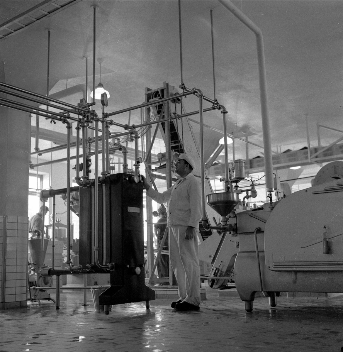Tørrmelkfabrikk i Brumunddal, Ringsaker, 15.10.1956, produksjonshall, fabrikkarbeider i forgrunnen. (Foto/Photo)