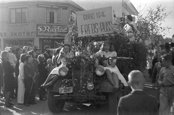 """17. mai 1945. Hamar. Nasjonaldag. Frigjøringen. Russetoget passerer forbi S. Rustads forretning i Torggata 42. Fredsdagene. Plakat """"Fredsruss anno 1945. """" (Foto/Photo)"""