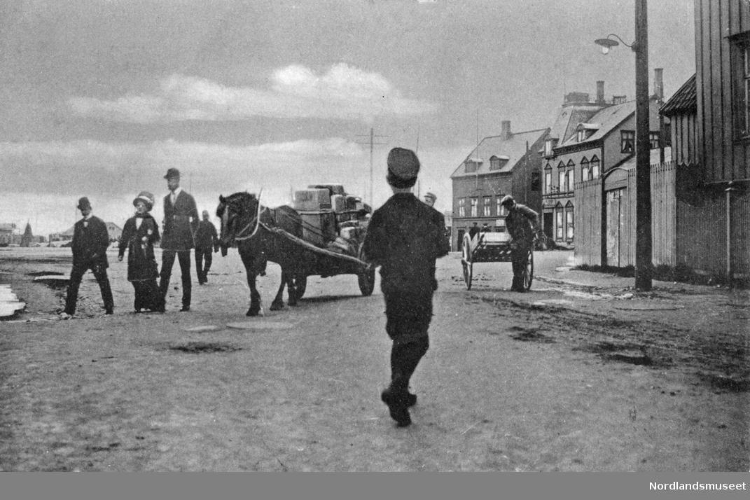 Gatebilde ved Jakhellngården. Barn og voksne. 1 hest med kjerre og en mannsperson med ei håndkjerre. Bebyggelse t.h., Grand hotell. Se NM.F.001132-00001 (Foto/Photo)