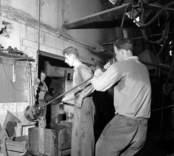 Tillverkning av prydnads- eller belysningsglas i Flygsfors glasbruk.  Glasblåsning är ibland fysiskt krävande, så därför är man här två personer som hjälps åt. En man som blåser, och en som välsar glaset för att forma det.  Flygsfors glasbruk grundades av Otto Hammargren 1863 och var i drift till 1979. Man tillverkade till en början bara fönsterglas, men gick senare över till belysnings- och prydnadsglas.
