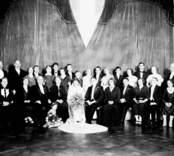 En gruppbild i bröllopsammanhang med ett brudpar i mitten. Enligt Walter Olsons journal är bilden beställd av ingenjör M Minqur ifrån Orrevägen 6 i Oskarshamn.