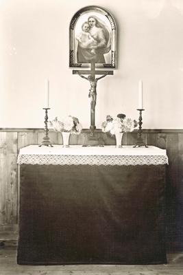 Ett litet altare av enklare modell, med krucifix och en ikonmålning föreställande Maria med Jesus.
