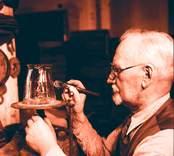En glasslipare drar upp stödlinjer på en karaff, som är upställd på en kavalett,  innan slipning.