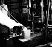 Formgjutning av glas, där en glasblåsare fångar an glas på en stor pipa, som sedan klipps ned i en form.