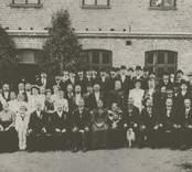Gruppbild utanför Stora sliperiet år 1909 med de nio medaljörerna, bolagsstyrelsen med flera.