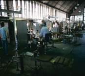 Glasblåsning vid Orrefors Glasbruk. En benmakare ska dra ut benet på ett vinglas, som först värmts i en invärmningsugn.
