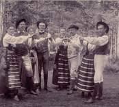 En grupp dansande människor i folkdräkter någonstans i Nybro.