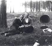 Mörtfors?  Musikstund i tallskogen.  Emil Karlssons bror Sixten tillsammans med okänd flicka lyssnande till musik från trattgrammofon.  Grammofonen tillhörde med säkerhet Emil Karlsson. Den förekommer i andra sammanhang på bilder från slutet av 1910-talet och 1920-talet. Tratten rikt figurpressad,  Det verkar som om skivorna förvarades i en trälåda med bl a tidningspapper som mellanlägg och skydd.