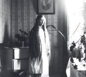 Bilden visar Elsa Alexandersson, Bäckfall. Ev. kan fotot vara taget i en lägenhet i Elimkyrkan i Mörtfors. Den ramade bilden på väggen visar Elsas far skräddaremästare Sander Eriksson.