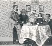 Familj runt finbordet. Fadern håller en fiol.