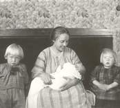 Fru Greta Johansson Myrsäter flankerad av barnen Ivan, född 1920 och Ingrid född 1921 gift Persson, och liggande i knät sonen Sven född 1923.