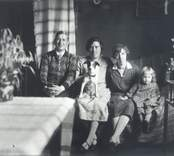 Från vänster: Folkskolläraren Helge Schlyter. Märta Nikolausson, född Lindström fru Linnéa Schlyter dottern Birgit (Bibbi) samt släthåriga terriern Bella. Fotot taget i lärarbostadens vardagsrum.