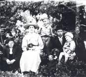 Familjen Gustaf Fr. Karlsson fotograferade i närheten av Garveriet, Soldatström.  1. Gustaf Fr. Karlsson f. 1877-03-09 + 1969-01-05 2. Makan Anna A. f. Dahlkvist 1882-09-19 + 1959-09-20  3. Nore f. 1905-09-05 4. Karl f. 1914-02-23 5. Herman f. 1916 + 1927 6. Sören f. 1907-10-28 7 hunden Ulla och hennes valp (8).