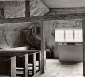 """Interiör från Väderskärs kapell. Byggt 1590 och flyttat till platsen 1615.  """"Kapellet är ett lågt timmerhus med ett stort vapenhus med dörr i väster. Det är knuttumrat med inklädda knutar, klätt med stående panel troligen på 1700-talet. I inredningen, som är helt av trä, finns enkla rakryggade bänkar där det på flera platser finns inskurna bomärken. Altaret är ett enkelt, framtill klätt bord som även tjänar som predikstol. Väggar och tak är till största delen målade och målningarna är av två slag. En enklare typ av målning i allmogestil finns huvudsakligen i tak och gavlar. De framställer bla en Golgatascen, änglar, skepp mm och är daterade 1740. Övriga delar av kapellets innerväggar panelades förmodligen 1738 med redan förut målade brädor. Bland dessa kan bla urskiljas Kristi dop, Kristi uppståndelse mm. Numera utnyttjas kapellet till sommargudstjänster och bröllop bla. Genom länsstyrelsens beslut 1980 blev det ett byggnadsminne.""""  (hämtat från Nationalencyklopedin.)"""
