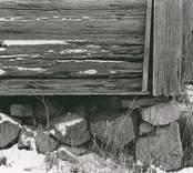 Detalj av husgrunden på en stuga utförd i liggtimmer med korsknut.