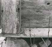 Detalj av husgrunden på en stuga i liggtimmer.
