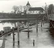 Hjorteds kyrka med dammbyggnad och bro i förgrunden.