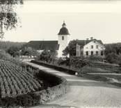 Hjorteds kyrka och skola. En trädgård skymtar till vänster.
