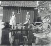 Tvättning av kläder vid Hvilan 1935.  Agda och Ebba vid byken. Agda Blomquist och Ebba Hallberg med dottern Ruth.