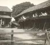 En gård med bostadshus och bod med loftgång till höger.