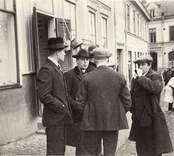 """Utanför café """"Ettan"""" i Widenborgska huset vid Salutorgets norra sida. Waernqvists korgar hänger som skylt till korgmakeriet. Vanligen stod Waernqvistskan på torget vid ett torgbord och sålde. I bakgrunden Stadskällaren, Södern nuvarande Frejamagasinet."""