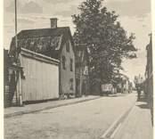 Vykort med motiv från Hamngatan i Västervik. Fotot är retuscherat. Bland annat är skugga borttagen moln ditlagda och flaggstången ifylld Samhörig med Västervik111A som är originalbild.