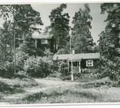 Vy på  Hjorted Misterhults s.n, Mörtfors badort, stugor med omgivande träd.