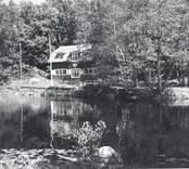 Vy från Hjorted och Misterhults s.r, Mörtfors vandrarhem på andra sidan ån.