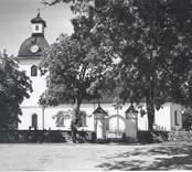 Vy över Kristdala kyrka med portalen till kyrkogården.