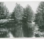 Vy över  Hjorted och Misterhults s.r, Mörtfors badrestaurang, med ån rinnande framför.