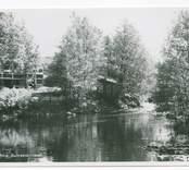 Vy över Hjorted och Misterhults s.r, Mörtfors badrestaurang, med ån framför restaurangen.