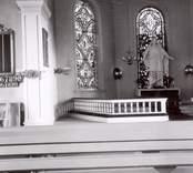 Interiören av Madesjö kyrka. Kyrkbänkar, kyrkfönster, altarring och altaruppsats.