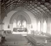 Interiör av Fagerhults kyrka. Långhus med kyrkbänkar. Kor och absid.