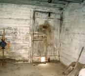 Interiör brygghus - grovkök, ingång från gamla husets gavel direkt till grovkök med vattenpump, vitkalkade väggar.