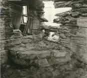 Interiör från ett fallfärdigt hus med eldstad.