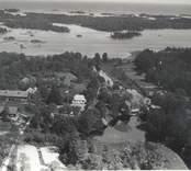 Flygfoto över Misterhult sn, Virbo. Samhället med hus och ekonomibyggnader samt grusvägen och sjön i bakgrunden.