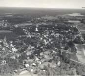 Flygfoto över Kristdala socken, Kristdala. Samhället med hus, kyrka och grusväg.