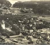 Överblick på samhället med kyrkan och grusvägen och bostadshus.