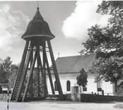 En klockstapel vid en kyrka i nyklassicistisk stil. Karlslunda socken.