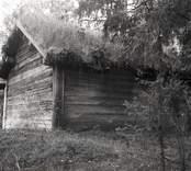 En ekonomibyggnad med timmervägg och torvtak.