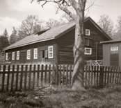 En ladugård med timmervägg och ett staket.