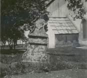 Källa ödekyrka med sakristian i bakgrunden och en gravsten i förgrunden.