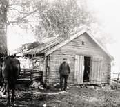 Mannen utanför smedjan och hästen till vänster.
