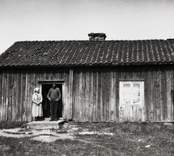 Farshults soldattorp, exteriör med hustru Gustava Front och soldaten Karl August Front på trappan.