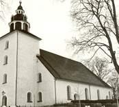 Odensvi kyrka med kyrkogården i förgrunden.