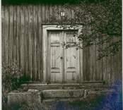 Malghult 1:38. Dörr med trappa till ett bostadshus med träfasad.