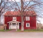 Rödmålat bostadshus med veranda i Hälleberga.